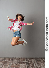 Full-length portrait of pretty jumping girl in casual wear, showing thumb up gesture