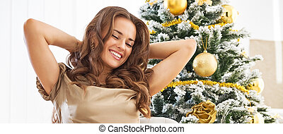 Full length portrait of relaxed young woman sitting near christmas tree
