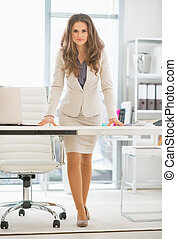 Full length portrait of serious business woman standing in office