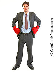 Full length portrait of serious modern businessman in boxing gloves