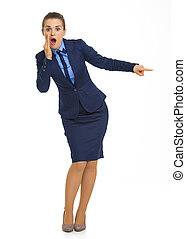 Full length portrait of shocked business woman pointing on copy space