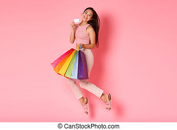 Full length portrait of silly and cute glamour asian girl love wasting money in stores, showing her credit card and jumping happy, holding shopping bags, buying new clothes, pink background