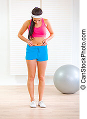 Full length portrait of slim young woman checking her body fat