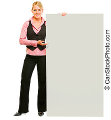 Full length portrait of smiling business woman pointing on blank board isolated on white