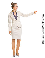 Full length portrait of smiling business woman pointing on copy space