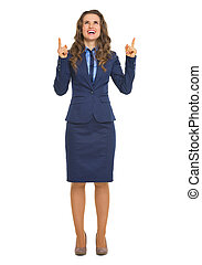 Full length portrait of smiling business woman pointing up on copy space