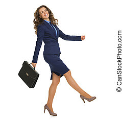 Full length portrait of smiling business woman with briefcase cheerfully going sideways