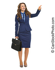 Full length portrait of smiling business woman with briefcase pointing on copy space