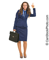 Full length portrait of smiling business woman with briefcase pointing up on copy space