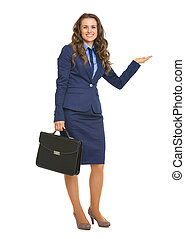 Full length portrait of smiling business woman with briefcase presenting something on empty palm