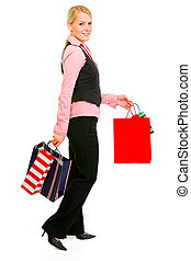 Full length portrait of smiling business woman with shopping bags isolated on white