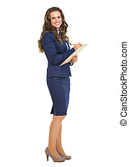 Full length portrait of smiling business woman writing in...