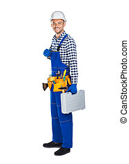 Full length portrait of smiling construction worker in uniform with toolbox