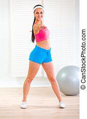 Full length portrait of smiling fitness girl making gymnastics at living room