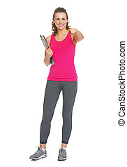 Full length portrait of smiling fitness trainer with clipboard pointing in camera