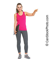 Full length portrait of smiling fitness trainer with clipboard pointing on copy space