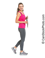 Full length portrait of smiling fitness trainer with clipboard