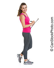 Full length portrait of smiling fitness trainer writing in clipboard