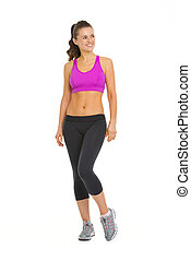 Full length portrait of smiling fitness young woman looking on copy space