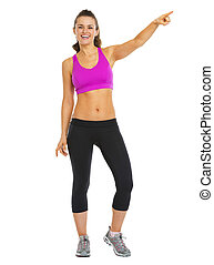 Full length portrait of smiling fitness young woman pointing on copy space