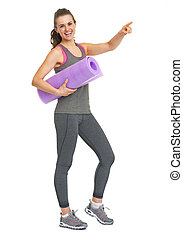 Full length portrait of smiling fitness young woman with fitness mat pointing on copy space