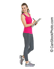 Full length portrait of smiling fitness young woman writing in clipboard and looking on copy space