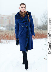 Full length portrait of smiling girl in blue coat at wintry ...