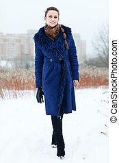 Full length portrait of smiling girl in blue coat at wintry park