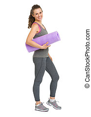Full length portrait of smiling healthy young woman with fitness mat