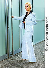 Full length portrait of smiling modern business woman entering office building