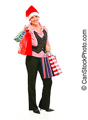 Full length portrait of smiling modern business woman in Santa Hat holding shopping bags isolated on white