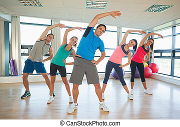 Full length portrait of smiling people doing power fitness exercise at yoga class in fitness studio