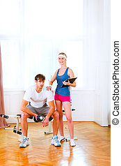 Full length portrait of smiling personal trainer working with client