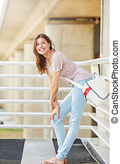 smiling woman with bag standing outside