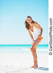 Full length portrait of smiling young woman applying sun...