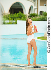 Full length portrait of smiling young woman with cocktail at poolside