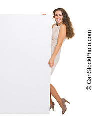 Full length portrait of smiling young woman holding blank billboard