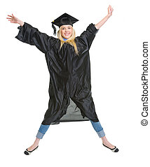 Full length portrait of smiling young woman in graduation gown jumping