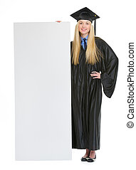 Full length portrait of smiling young woman in graduation gown showing blank billboard