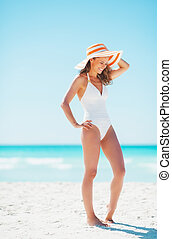 Full length portrait of smiling young woman in hat on beach