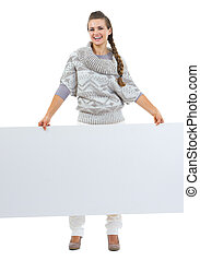 Full length portrait of smiling young woman in sweater holding blank billboard