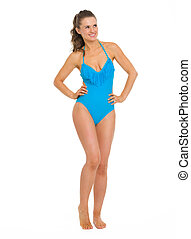 Full length portrait of smiling young woman in swimsuit looking on copy space