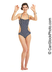 Full length portrait of smiling young woman in swimsuit showing
