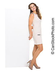 Full length portrait of smiling young woman showing blank billboard