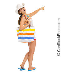 Full length portrait of smiling young woman with beach bag pointing on copy space