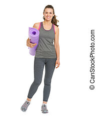 Full length portrait of smiling young woman with fitness mat