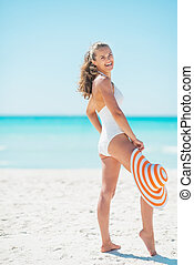 Full length portrait of smiling young woman with hat on beach
