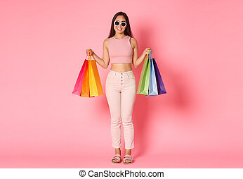 Full length portrait of stylish, pretty asian woman travelling abroad and buying souvenirs, new clothes in stores, carry shopping bags, wearing sunglasses and smiling over pink background