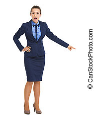 Full length portrait of surprised business woman pointing on copy space