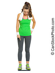 Full length portrait of surprised fitness young woman standing on scales